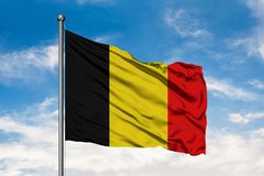 Flaga Belgia falowanie w wiatrze przeciw białemu chmurnemu niebieskiemu niebu belgijska flag? fotografia royalty free