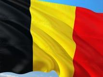 Flaga Belgia falowanie w wiatrze przeciw g??bokiemu niebieskiemu niebu Wysokiej jako?ci tkanina zdjęcie royalty free