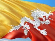 Flaga Bhutan falowanie w wiatrze przeciw g??bokiemu niebieskiemu niebu Wysokiej jako?ci tkanina obraz stock