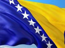 Flaga Bośnia i Herzegovina falowanie w wiatrze przeciw głębokiemu niebieskiemu niebu Wysokiej jako?ci tkanina zdjęcie stock