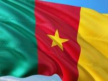 Flaga Cameroon falowanie w wiatrze przeciw g??bokiemu niebieskiemu niebu Wysokiej jako?ci tkanina obraz royalty free