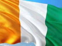 Flaga Cote d ?Ivoire falowanie w wiatrze przeciw g??bokiemu niebieskiemu niebu Wysokiej jako?ci tkanina zdjęcia royalty free