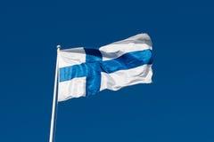 Flaga Finlandia przed niebieskim niebem. Zdjęcia Royalty Free