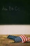 Flaga kłaść na górze starej szkoły biurka Zdjęcia Stock