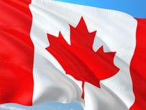Flaga Kanada falowanie w wiatrze przeciw g??bokiemu niebieskiemu niebu Wysokiej jako?ci tkanina fotografia stock