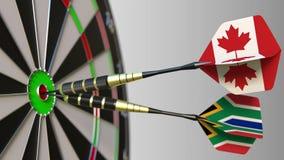 Flaga Kanada i Południowa Afryka na strzałkach uderza bullseye cel Międzynarodowy współpraca lub rywalizacja Obraz Stock