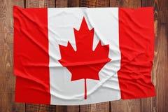 Flaga Kanada na drewnianym sto?owym tle Marszcz?cy kanadyjczyk flagi odg?rny widok zdjęcie royalty free
