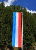 Flaga Luksemburg przeciw lasu i niebieskiego nieba tłu fotografia stock
