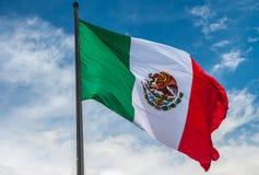 Flaga Meksyk nad błękitnym chmurnym niebem zdjęcia royalty free