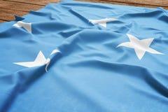 Flaga Micronesia na drewnianym biurka tle Jedwabniczy Micronesian chor?gwiany odg?rny widok obrazy stock
