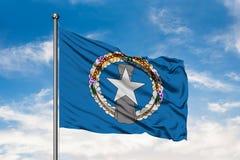 Flaga Północne Mariana wyspy macha w wiatrze przeciw białemu chmurnemu niebieskiemu niebu fotografia stock