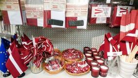 Flaga państowowa Latvia, inni krajowi symbole i pamiątki na półce sklepowej, Ryski, Latvia, Luty 9, 2017 Zdjęcia Royalty Free