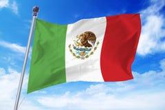 Flaga rozwija przeciw jasnemu niebieskiemu niebu Meksyk Zdjęcia Royalty Free