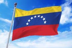 Flaga rozwija przeciw jasnemu niebieskiemu niebu Wenezuela Fotografia Stock
