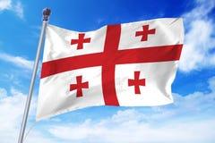 Flaga rozwija przeciw niebieskiemu niebu Gruzja Fotografia Stock