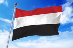 Flaga rozwija przeciw niebieskiemu niebu Jemen Fotografia Stock