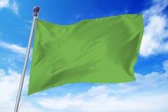 Flaga rozwija przeciw niebieskiemu niebu Libia Zdjęcia Stock