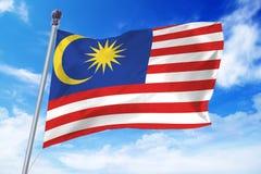Flaga rozwija przeciw niebieskiemu niebu Malezja Obrazy Stock