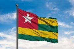Flaga Togo falowanie w wiatrze przeciw białemu chmurnemu niebieskiemu niebu Togolese flaga fotografia stock