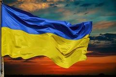 Flaga Ukraina przeciw niebu przy zmierzchem Obrazy Royalty Free