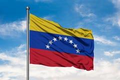 Flaga Wenezuela falowanie w wiatrze przeciw białemu chmurnemu niebieskiemu niebu wenezuelczyk bandery fotografia royalty free
