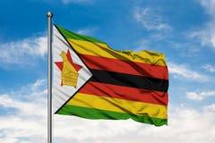 Flaga Zimbabwe falowanie w wiatrze przeciw białemu chmurnemu niebieskiemu niebu Mieszkaniec Zimbabwe flaga zdjęcie royalty free