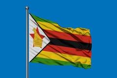 Flaga Zimbabwe falowanie w wiatrze przeciw głębokiemu niebieskiemu niebu Mieszkaniec Zimbabwe flaga obraz royalty free