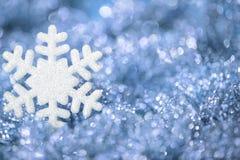 Flagar blå bakgrund för snöflingan som mousserar snö, garnering Arkivfoton