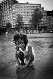 Flagey正方形的黑人女孩在雨以后的在热 库存照片