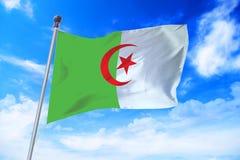 Flagga av Algeriet som framkallar mot en blå himmel Arkivfoto