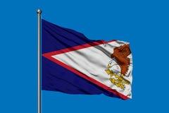Flagga av American Samoa som vinkar i vinden mot djupblå himmel royaltyfri illustrationer