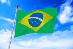 Flagga av Brasilien som framkallar mot en blå himmel Royaltyfri Fotografi