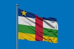 Flagga av Centralafrikanska republiken som vinkar i vinden mot djupblå himmel royaltyfri fotografi