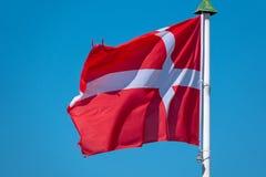 flagga av Danmark som bl?ser f?r en bl? himmel arkivbild