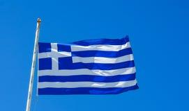 Flagga av det Grekland flyget i vind och blå himmel Royaltyfri Foto