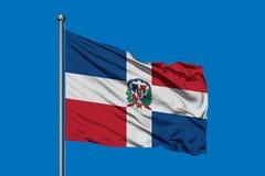 Flagga av Dominikanska republiken som vinkar i vinden mot djupblå himmel Dominikansk flagga royaltyfri illustrationer