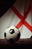 Flagga av England med fotboll på träbräden royaltyfri fotografi