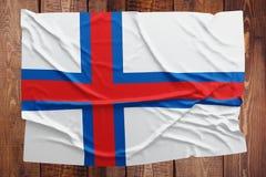 Flagga av Faroe Island p? en tr?tabellbakgrund B?sta sikt f?r rynkig flagga royaltyfri bild