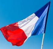 Flagga av Frankrike mot den blåa himlen Arkivbild
