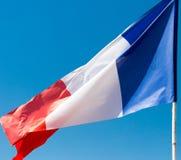 Flagga av Frankrike mot den blåa himlen Arkivfoto