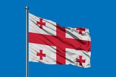 Flagga av Georgia som vinkar i vinden mot djupblå himmel georgian flagga arkivbilder