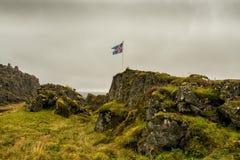 Flagga av Island som framkallar i vinden bland det steniga lösa landskapet Fotografering för Bildbyråer