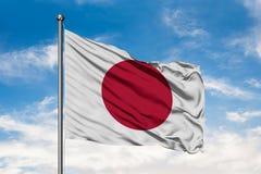 Flagga av Japan som vinkar i vinden mot vit molnig blå himmel Japanen sjunker royaltyfri bild