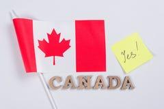 Flagga av Kanada, ord Kanada i träabstrakta bokstäver, klistermärke med inskriften ja Fotografering för Bildbyråer