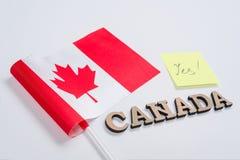 Flagga av Kanada, ord Kanada i träabstrakta bokstäver, klistermärke med inskriften ja Vit bakgrund Royaltyfri Foto