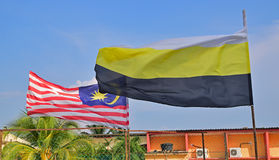 Flagga av Malaysia som vinkar i luften samman med flagga av den Perak staten i förgrunden Royaltyfri Foto