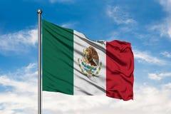 Flagga av Mexico som vinkar i vinden mot vit molnig blå himmel Mexikanen sjunker arkivbilder