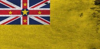Flagga av Niue på träplattabakgrund Niuisk flaggatextur för Grunge arkivbild