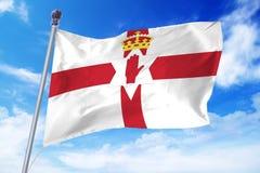 Flagga av nordligt - Irland som framkallar mot en klar blå himmel Royaltyfria Bilder