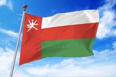 Flagga av Oman som framkallar mot en klar blå himmel Royaltyfri Bild